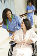 Nurse pushing patient in wheelchair in hospital