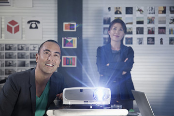 Japanese co-workers working with projector