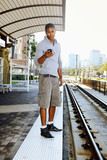 Man using cell phone on train platform