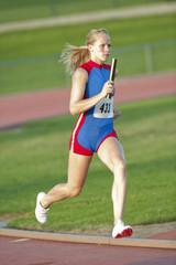 Caucasian runner holding baton running on track