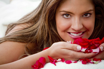 Hispanic woman smelling rose petals