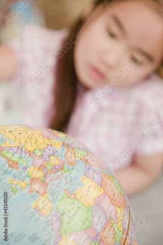 Japanese girl looking at globe