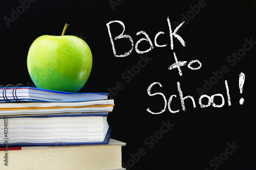 Back to School written on blackboard, books and apple in front