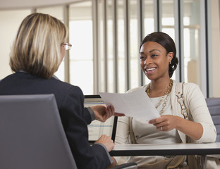 Businesswoman handing paper to co-worker