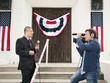 Camera man filming news reporter with American flag decorations in background