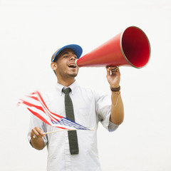 Hispanic man waving American flag and talking into megaphone