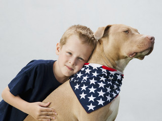 Caucasian boy hugging dog in American flag neckerchief