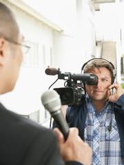 Camera man filming news reporter