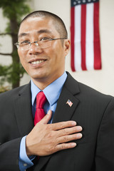 Chinese businessman pledging allegiance to American flag