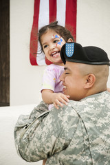 Hispanic soldier holding daughter in front of American flag