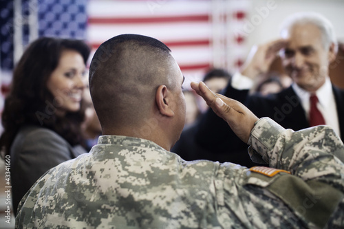 Soldier saluting politician at political gathering