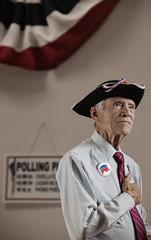 Caucasian man pledging allegiance in polling place