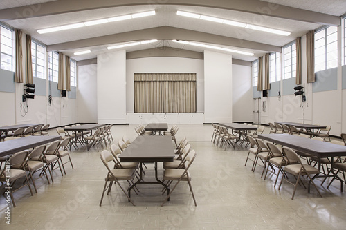 Tables and chairs in empty cafeteria with stage in background