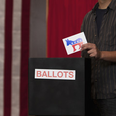 Voter putting ballot into ballot box at polling place