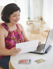 Hispanic woman holding paper and using laptop