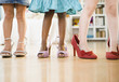 Girls trying on glamorous high-heeled shoes