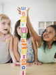 Girls stacking alphabet blocks together