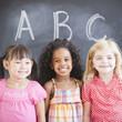 Smiling girls standing near blackboard