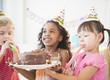 Girls holding birthday cake together