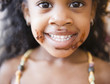 Mixed race girl with chocolate on her face