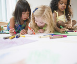Children laying on floor coloring together