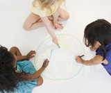 Girls sitting on floor drawing globe together