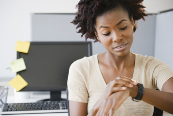 Black businesswoman checking the time at desk