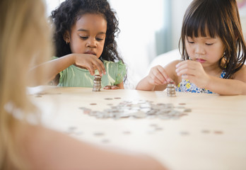 Girls stacking coins together