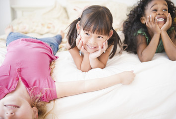 Smiling girls laying on bed together
