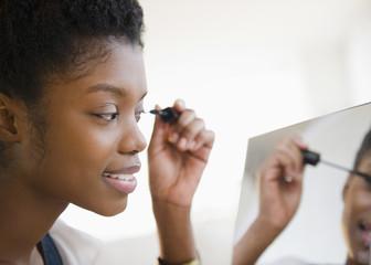 Black woman putting on mascara