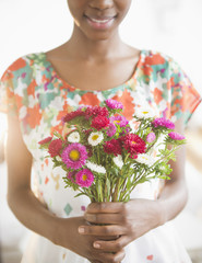 Black woman holding bouquet of flowers