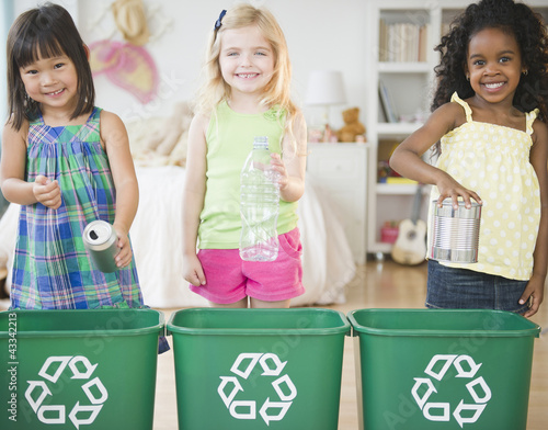 Children putting recyclable materials into recycling bins