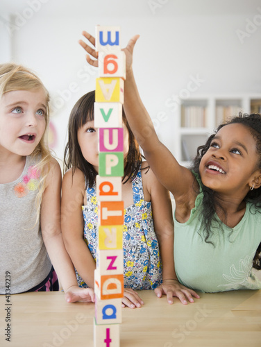 Girls stacking alphabet blocks together
