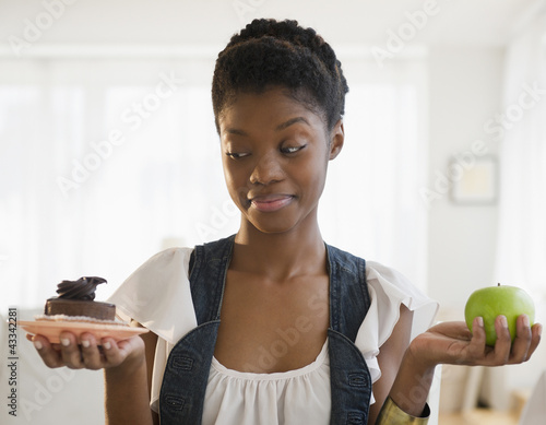 Black woman deciding between chocolate cake and apple