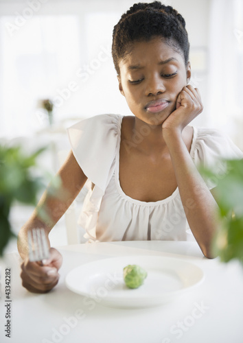 Frustrated Black woman looking at brussels sprout