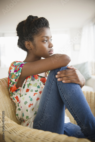 Serious Black woman sitting in chair