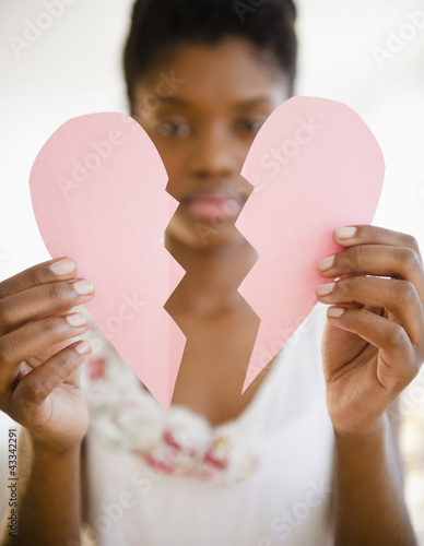 Black woman holding broken paper heart