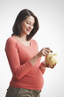 Pregnant Caucasian woman putting money into piggy bank