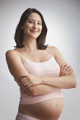 Pregnant Caucasian woman standing with arms crossed