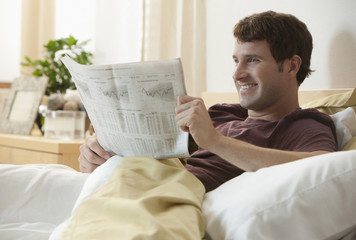 Caucasian man relaxing in bed reading newspaper