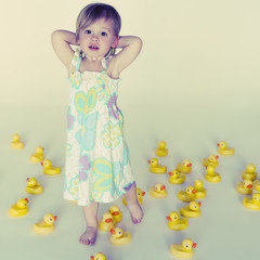 Caucasian girl standing with lots of rubber ducks