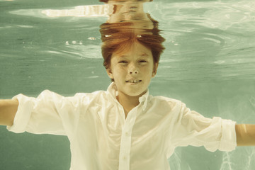 Boy in shirt swimming underwater in swimming pool