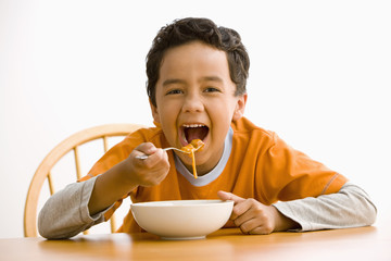 Hispanic boy eating pasta