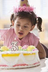 Hispanic girl blowing out candle on birthday cake