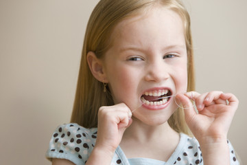 Girl flossing teeth with dental floss