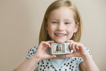 Girl holding digital camera with self-portrait