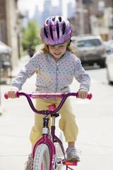 Girl riding bicycle on urban sidewalk