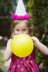 Girl in party hat blowing up balloon