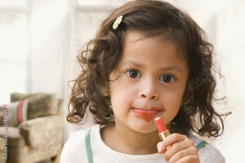Hispanic girl putting on lipstick