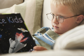 Caucasian boy reading space book